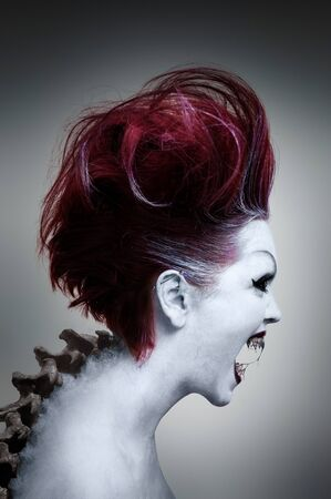 Portrait of an undead girl with red hair, white skin, black eyes, sharp fangs and spine sticking out of her back Archivio Fotografico