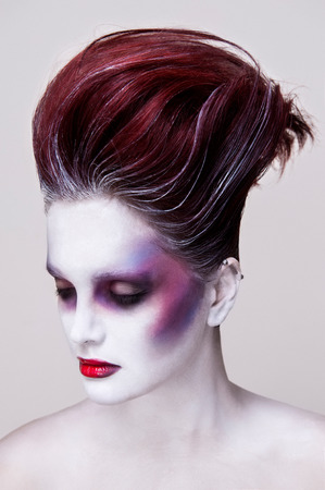 undead: Portrait of a girl with red hair wearing an undead makeup with purple cheeks, red lips and white skin. Her eyes are closed