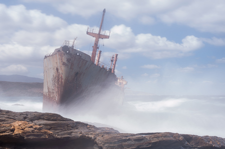 wheelhouse: Abandoned, covered in rust shipwreck being hit with huge waves during a sea storm on Andros island in Greece