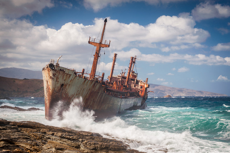 andros: Abandoned, covered in rust shipwreck being hit with huge waves during a sea storm on Andros island in Greece