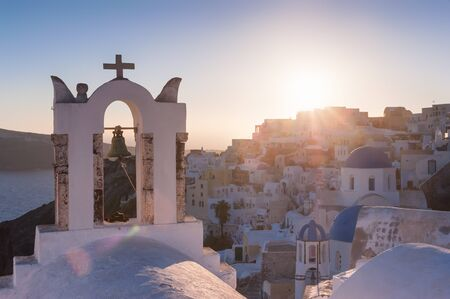firostefani: Church belfry in Firostefani during a sunset with the city and setting sun in the background, Santorini, Greece