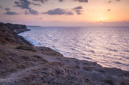 Sunset shots of a coastline of northern peninsula of Santorini island in Greece with the sun setting down the horizon photo