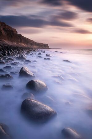 long shots: Long exposure shots of a rocky beach on northern peninsula of Santorini island in Greece during a sunset