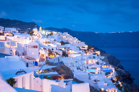 Evening view on Oia city, Santorini with typical greek white and illuminated buildings in the night photo