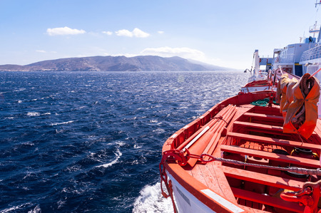 lifeboats: View on a blue sea and an island in Greece with lifeboats on the foreground and the clear sunny sky in the back