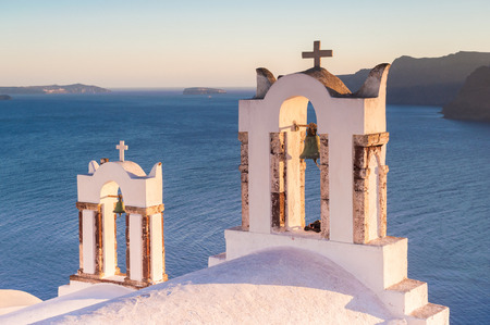 firostefani: Church belfry in Firostefani during a sunset with the Aegian sea in the background, Santorini, Greece Stock Photo