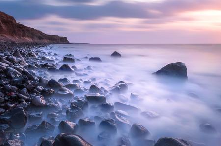 북부 반도의 산토리니 섬에 그리스에서 일몰 동안 바위 해변의 긴 노출 샷
