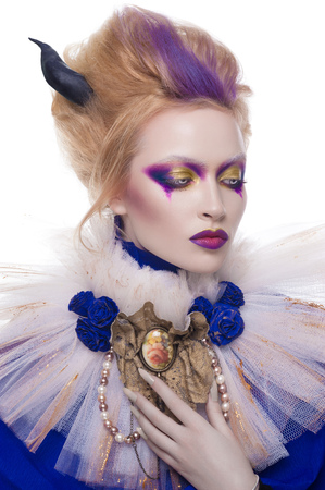 Studio beauty portrait of a girl with blonde hair wearing an undead makeup with purple eye shadows, purple lips and pale skin. Vampire queen halloween costume of a girl wearing a veil