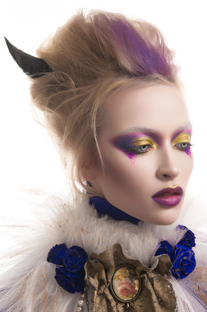 Studio beauty portrait of a girl with blonde hair wearing an undead makeup with purple eye shadows, purple lips and pale skin. Vampire queen halloween costume of a girl with horns.