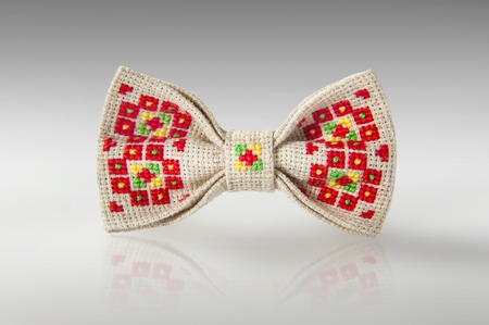 punto de cruz: Studio shot of a stylish beige bow-tie with a bright red, green and yellow ukrainian hand-made embroidery pattern on white background