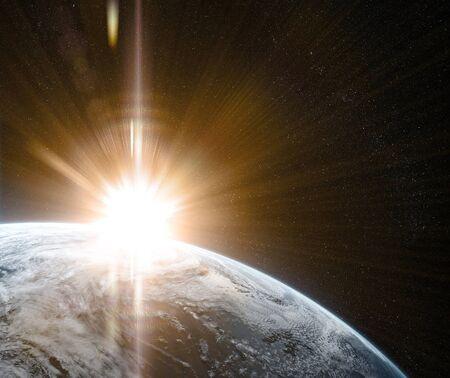 Sunrise in space with prominent sun flare and sun streaks. Orbital view on a planet covered in clouds from space. Planet is covered in clouds.