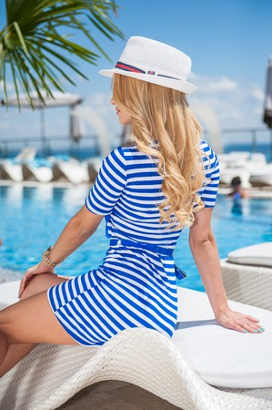 Young woman sitting near the pool in a dress and a hat under the hot summer sun