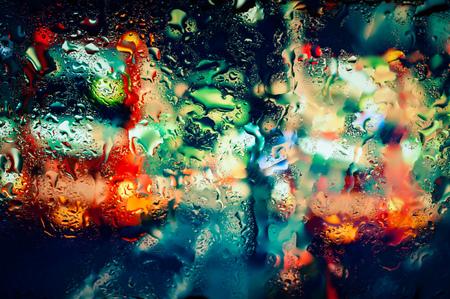 물방울과 젖은 유리를 통해 본 비에 흐린 밤 도시의 불빛 스톡 콘텐츠