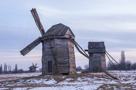 Landscape photo of old wooden windmills on a winter cloudy day