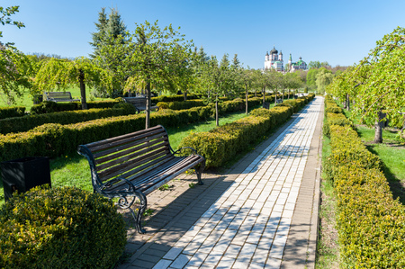 Bench and a pavement sidewalk in Feofania park, Kyiv, Ukraine with the Female St. Panteleimon Monastery in the background