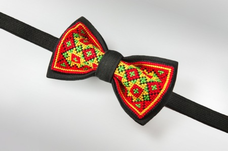 Studio shot of a stylish black bow-tie with a bright red, green and yellow ukrainian hand-made embroidery pattern on white background