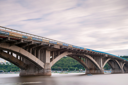 Subway bridge over the river Dniepr in Kiev, Ukraine. Long exposure shot with smooth water and cloudy sky.