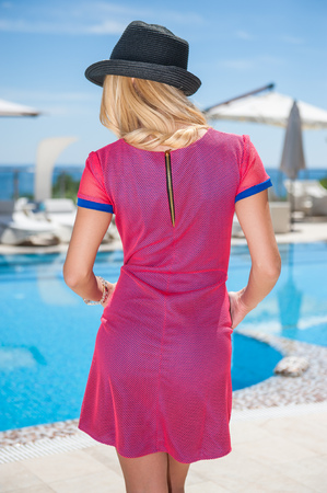 Young woman standing near the pool in a dress and a hat under the hot summer sun