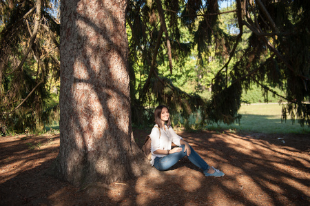 Young and pretty ukrainian girl sitting under a huge pine tree, enjoying the summer sun rays. Tourist ukrainian girl resting in a shade.