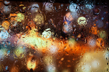 Blurry night city lights in the rain as seen through a wet glass with water droplets