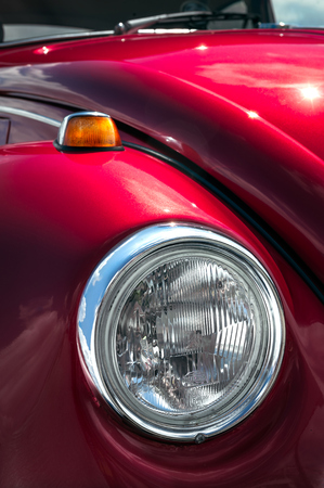 restored: Closeup shot of a head lamps of a bright red retro car