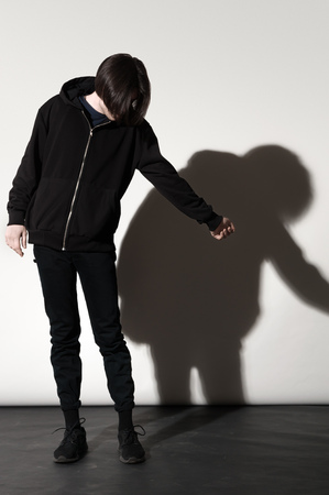 Contemporary Fashion portrait of young man posing against a white background with contrast shadows Standard-Bild