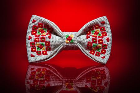빨간색 배경에 밝은 빨간색, 녹색 및 노란색 우크라이나어 손으로 만든 자 수 패턴과 세련 된 베이지 색 나비 넥타이 스튜디오 샷