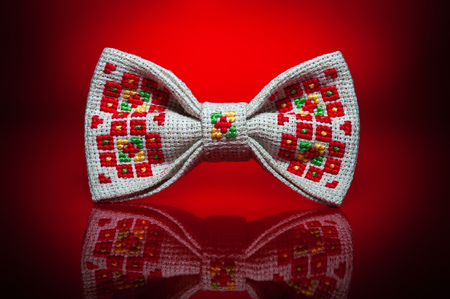 Studio shot of a stylish beige bow-tie with a bright red, green and yellow ukrainian hand-made embroidery pattern on red background Archivio Fotografico