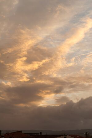 Vertical wide shot of dramatic sunset clouds. The main colors are orange, yellow and brown. Lots of copy space.