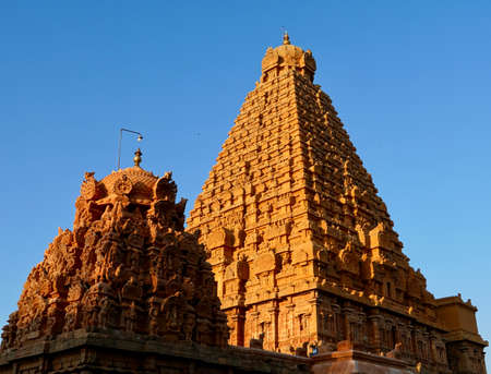 Brihadeeswarar temple in Thanjavur, Tamilnadu, India. Lord Shiva temple exterior tower against blue sky background. Ancient historical temple tower with Hindu God sculptures in Tamil nadu.