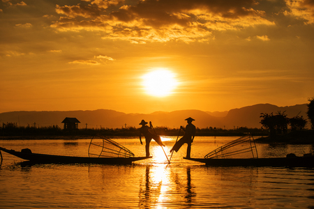 Inle fishermen are known for practising a distinctive rowing style which involves standing at the stern on one leg and wrapping the other leg around the boat paddle, Myanmar