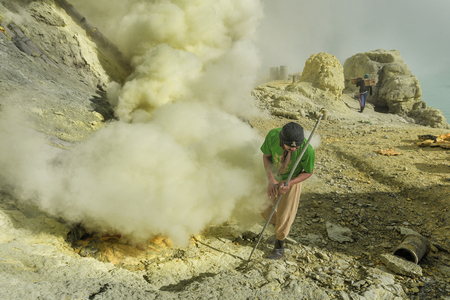 East Java, Indonesia June 2015: Sulphur miners involved in mining activities in Kawah Ijen volcano which is an active volcano has active vent at the edge of the lake is a source of elemental sulphur. Stock Photo
