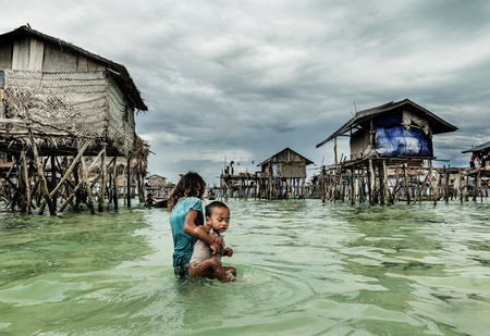 Bajau tribal girl carrying her brother to her home before he gets sunk in the sea, Sabah Semporna, Malaysia