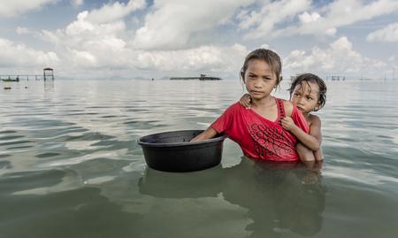 バジャウ族少女の保持コンテナーやアプローチの観光ボートの食べ物を食べる、マレーシア ・ サバ州センポルナを求めるため