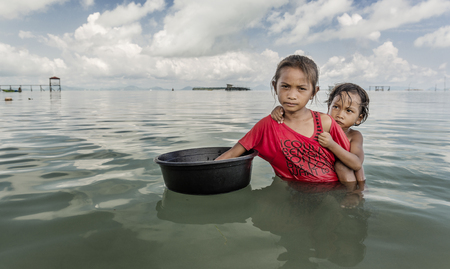 Bajau tribe little girl holding container and approached tourist boat for asking food to eat, Sabah Semporna, Malaysia