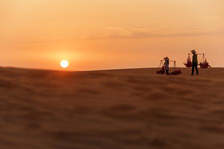 Woman carrying flower basket at sunset in Mui Ne sand dune, Vietnam