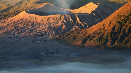 Mount Bromo glowing in golden light at sunrise, a popular tourist destination in Indonesia