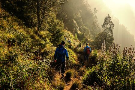 Tourists hiking down the mountain after enjoying the beautiful sunrise over Mount Bromo. Imagens