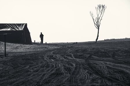 A lonely man standing outside his tent waiting for tourists at Mount Bromo parking lot after sunrise, Indonesia Imagens