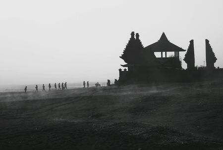 Silhouette of people walking to Hindu temple for morning prayers in Mount Bromo at sunrise