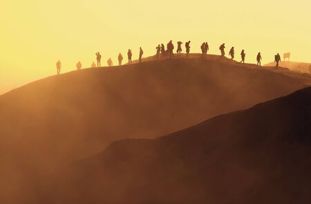 Tourists climbing to Mount Bromo volcano summit at sunrise Imagens