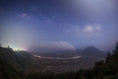 Mount Bromo covered with mist and milky way galaxy stars shining in the sky at night, Java Indonesia