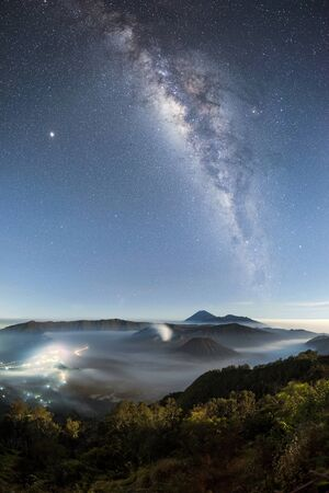Mount bromo covered with mist and milky way galaxy stars shining in sky at night, Java Indonesia, a vertical orientation shot Imagens