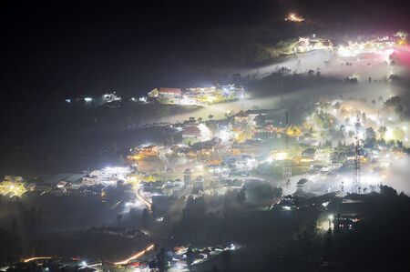 Mist flowing into a small village and trees near Mount Bromo at night