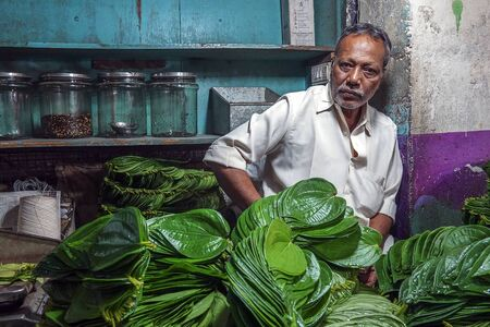 Indian men selling betel leaves and nuts at the basement of KR flower market Bangalore India which is one of the biggest flower markets in Asia