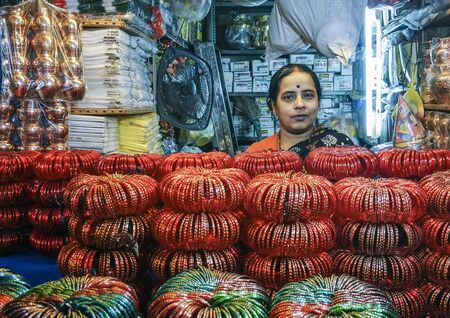 Indian woman selling bangles in a tiny shop at the basement of KR flower market Bangalore India which is one of the biggest flower markets in Asia