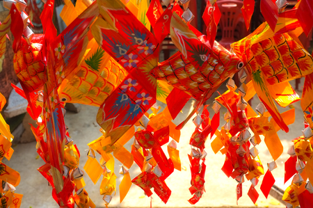 Thai-style fish mobiles (Pla ta pain). Plaited palm leaves and hand painted fish mobile. Small fish made from palm leaves, swinging over babys bed to put them to sleep.