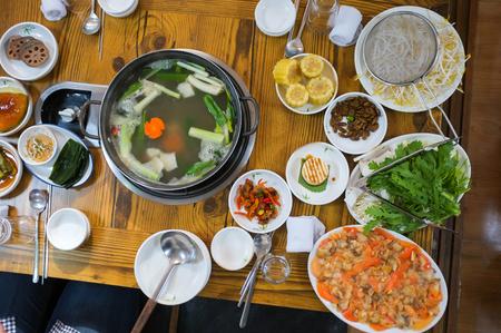 Korean food: Galmi Shabu Shabu with fresh raw Surf clam, kimchi, side dishes, and udon noodles Stock Photo