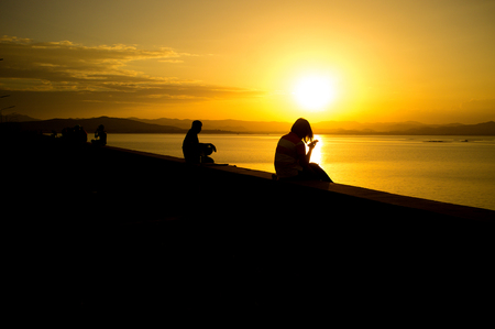 People are taking a rest on dam with sunset and some people using a smartphone to connect to social network or playing game.