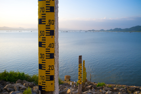 Drought crisis: Water level gauge or staff Gauge at Krasiew dam, Supanburi. Water meter showing the amount of water in the dam. Water level measurement. Stock Photo